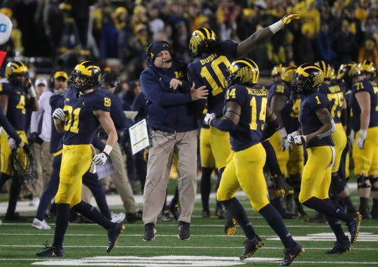 Michigan's Don Brown and Devin Bush celebrate after a stop during the second half against Indiana, Nov. 17, 2018 at Michigan Stadium.
