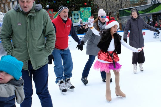 Dressed in a Santa's hat and antlers, Julissa Cornejo, 9, shows off her skills while spinning around the rink during opening weekend for the skating at Campus Martius Park in downtown Detroit on Sunday, November 18, 2018.