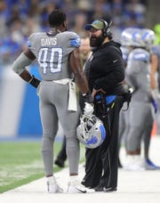 Matt Patricia talks with linebacker Jarrad Davis on Nov. 18 at Ford Field.