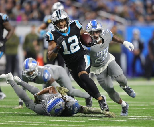 Panthers receiver DJ Moore runs with the ball against the Lions.