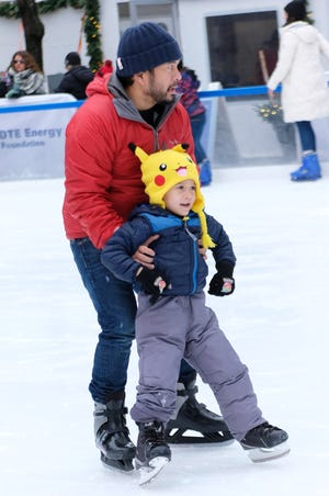 Lai Long helps his son Oliver, 4, both of Birmingham, as they take a lap around the link during opening weekend for the skating at Campus Martius Park in downtown Detroit on Sunday, November 18, 2018.