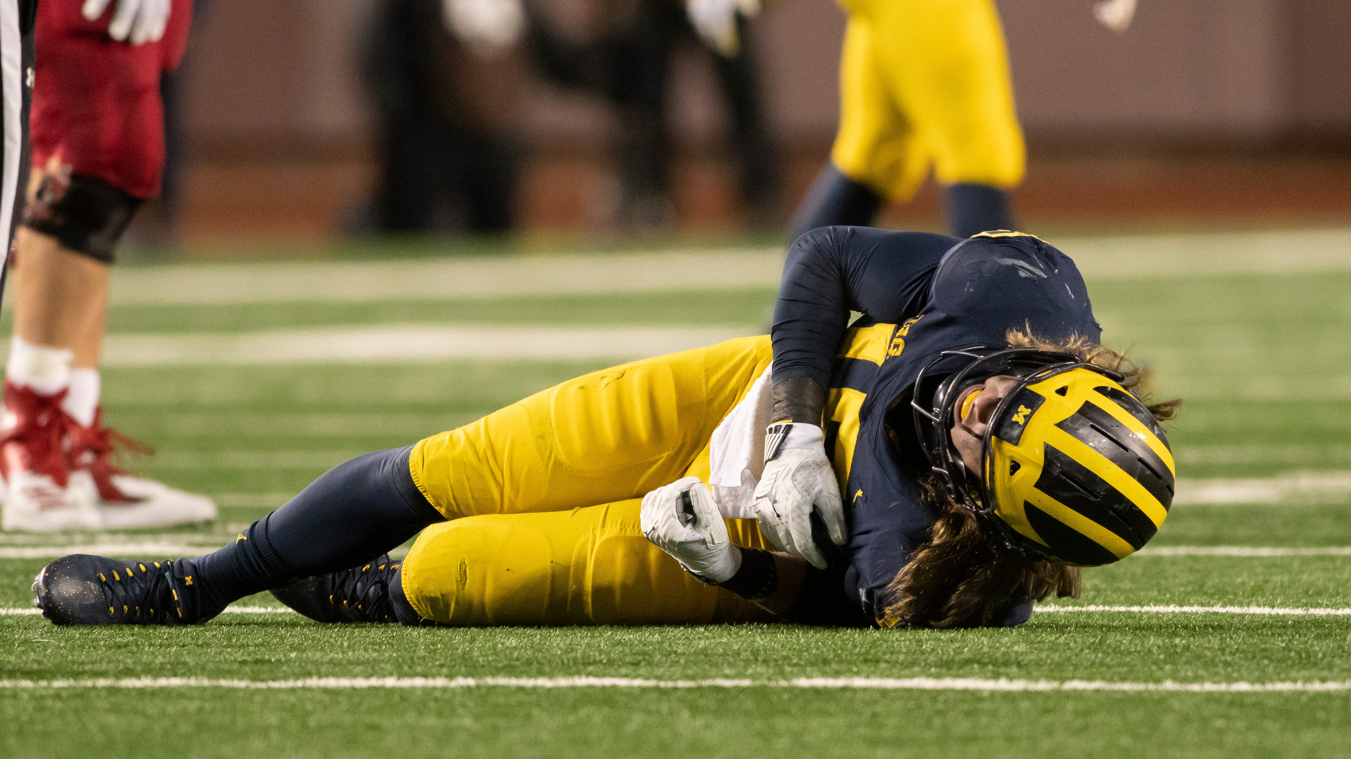 Michigan defensive lineman Chase Winovich lays on the ground after being injured in the third quarter.  Winovich left the game and did not return.