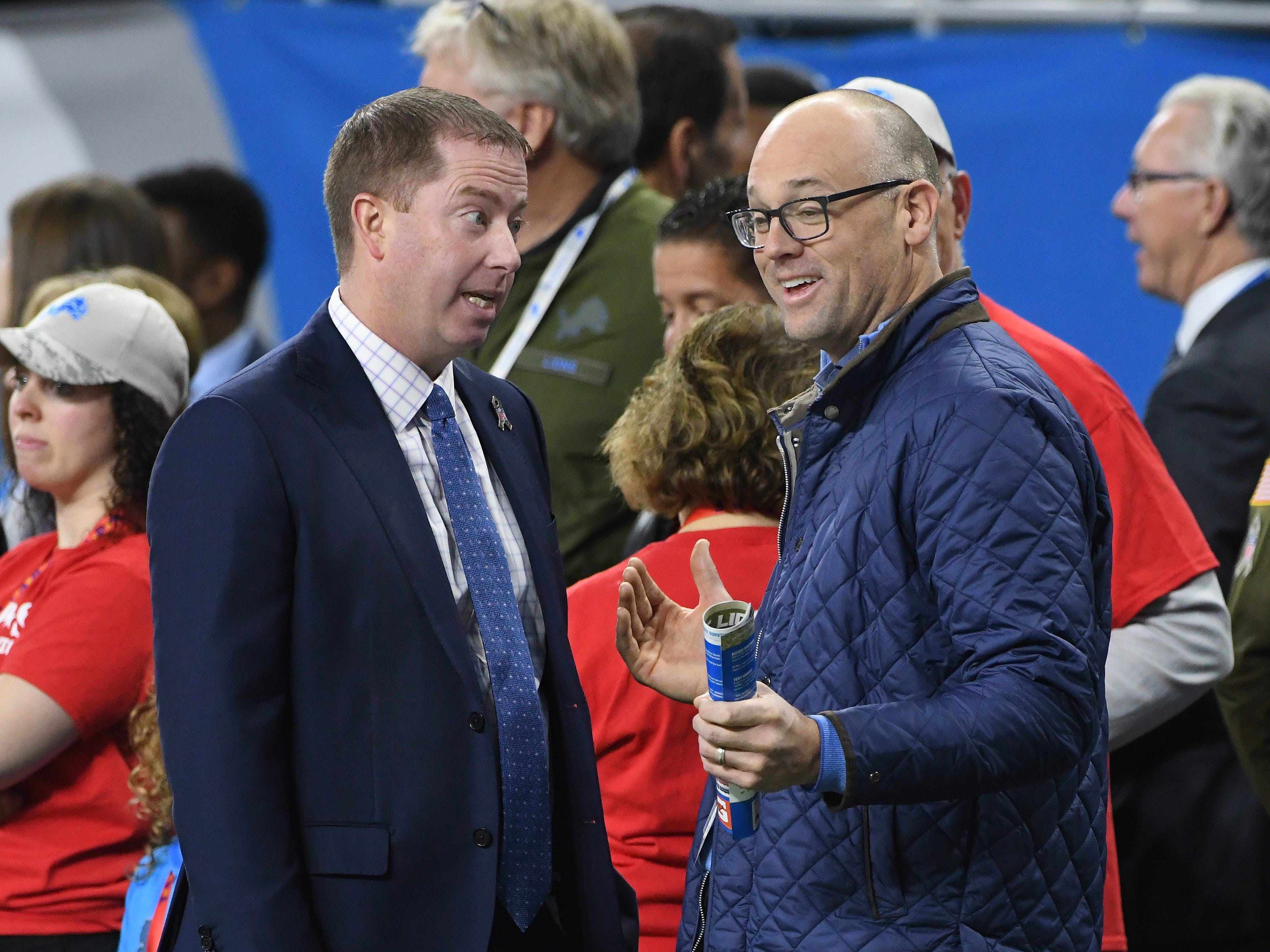 Lions general manager Bob Quinn and Detroit Red Wings coach Jeff Blashill chat on the sidelines during warm-ups before Detroit takes on Carolina at Ford Field.