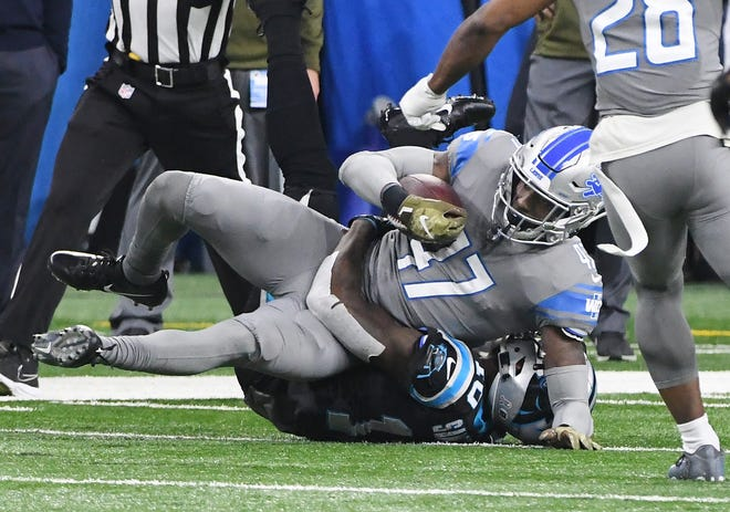 Lions safety Tracy Walker rips away a reception from the Panthers' Curtis Amuel for an interception last season.