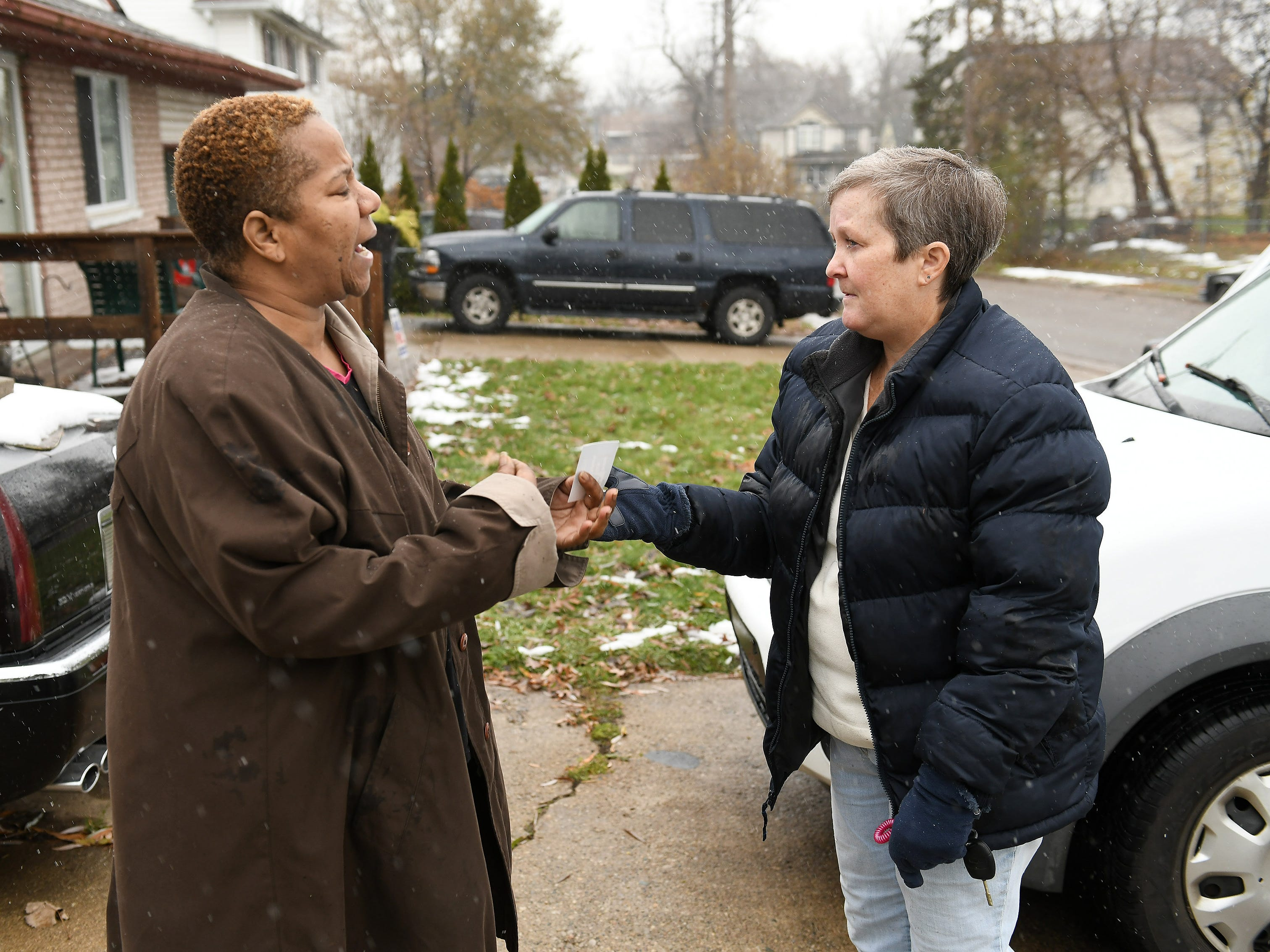 Animal Care Network manager Lori Elliott talks with Renee Greenhouse after Elliott and volunteers delivered fresh straw for Greenhouse's mother's dog in Pontiac.