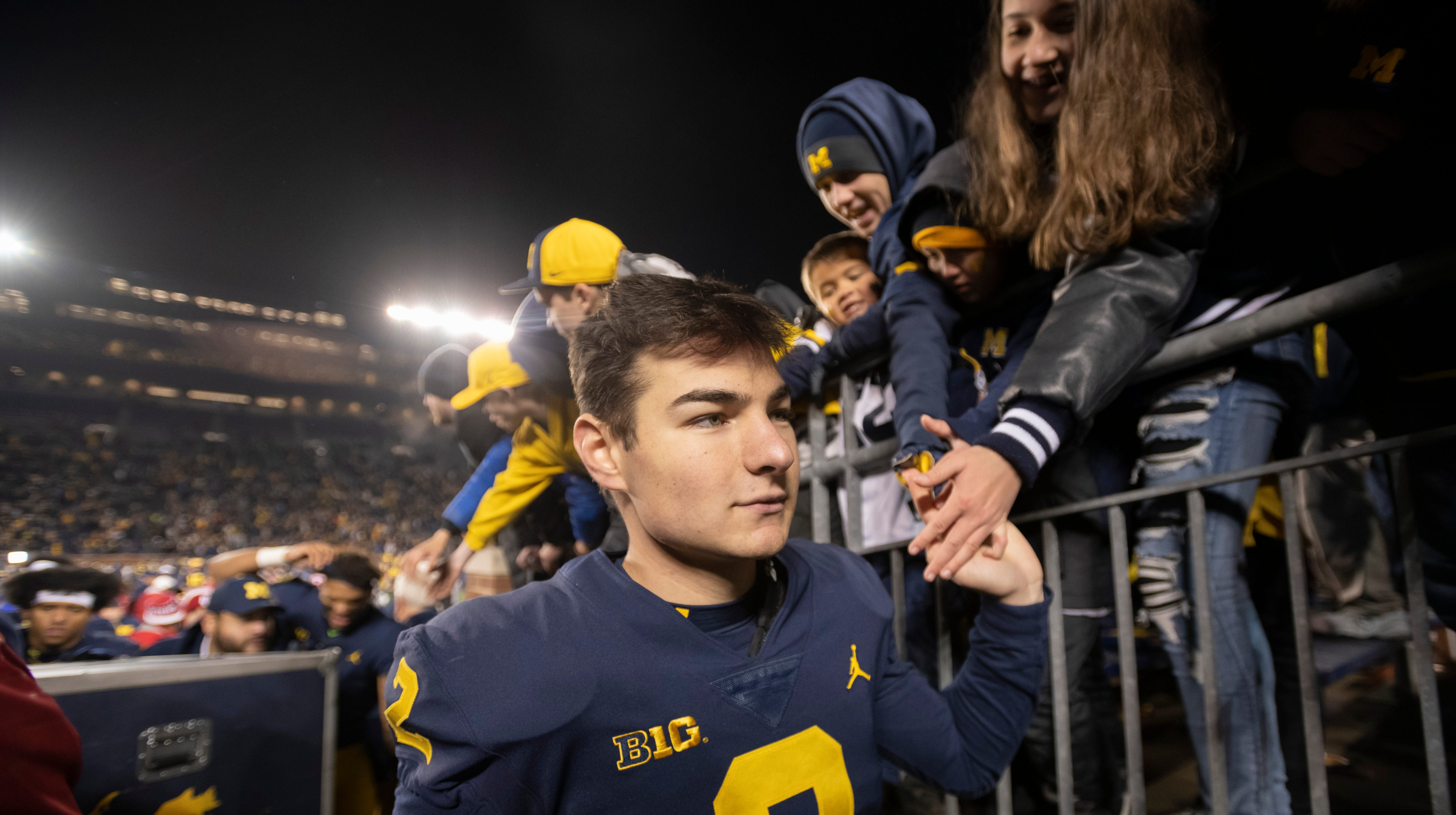 Michigan place kicker Jake Moody high-fives the fans after the game.
