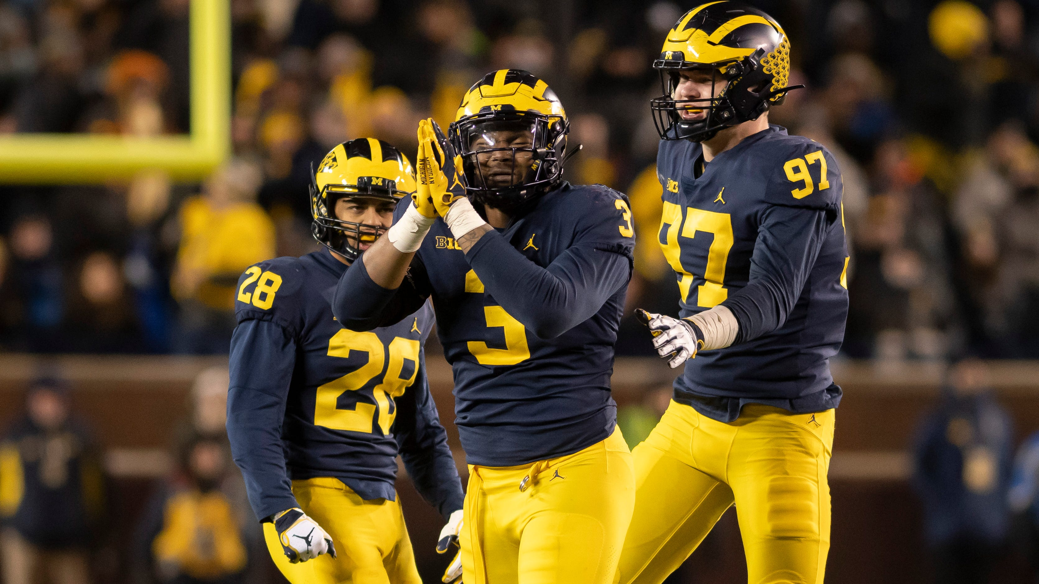 From left, Michigan defensive back Brandon Watson, defensive lineman Rashan Gary, and defensive lineman Aidan Hutchinson celebrate a sack late in the fourth quarter.