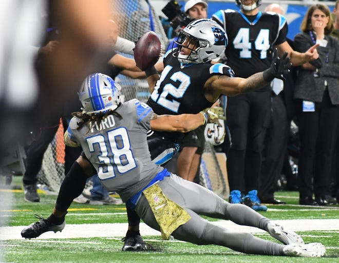 Panthers wide receiver DJ Moore brings down a reception in front of the Lions' Mike Ford in the third quarter.