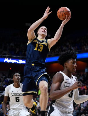 Michigan's Ignas Brazdeikis goes up to the basket between Providence's Jimmy Nichols Jr. (5) and David Duke (3) during the first half.
