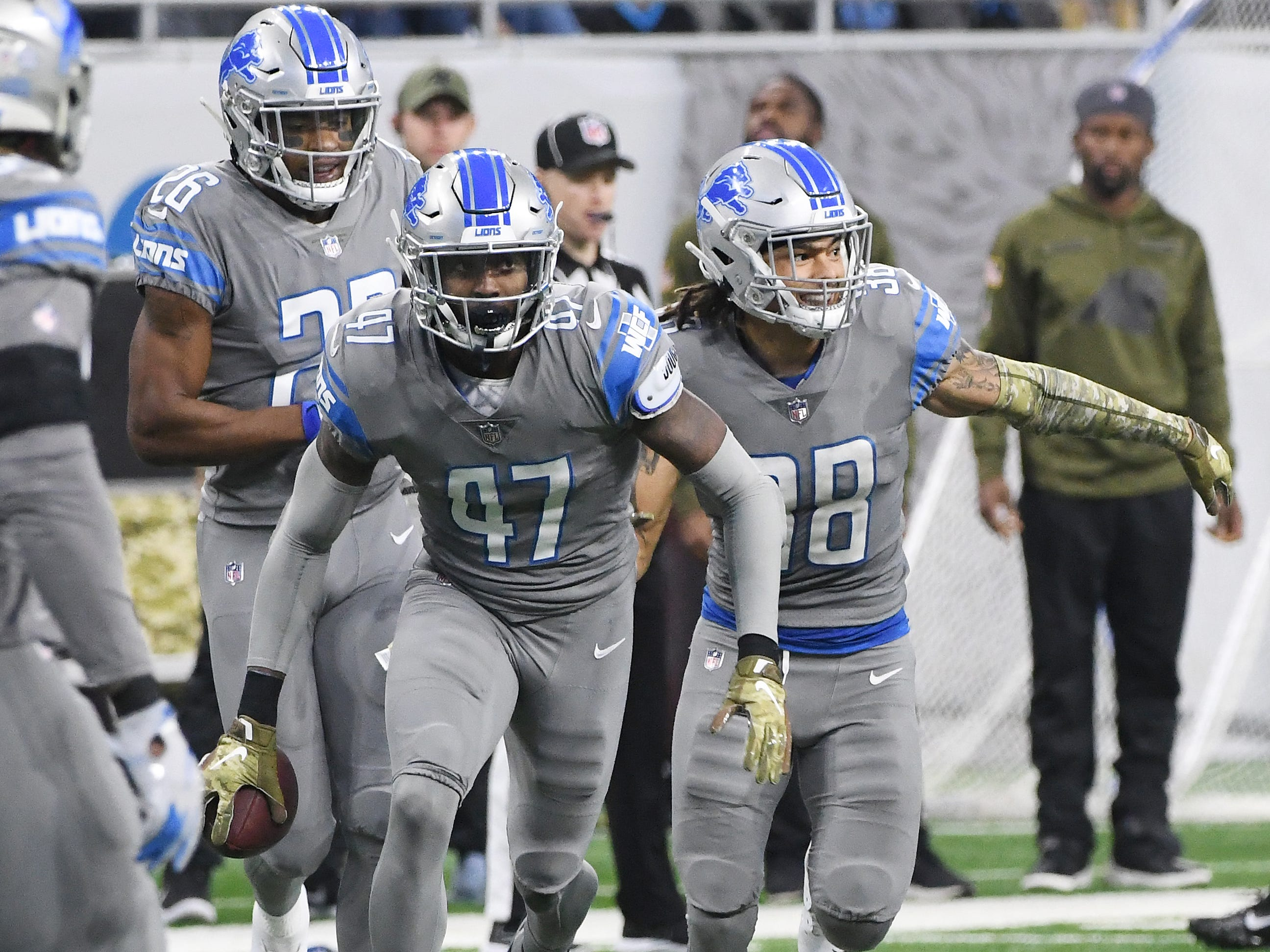 Lions teammates chase after Tracy Walker after intercepting a Panthers quarterback Cam Newton pass in the second quarter.