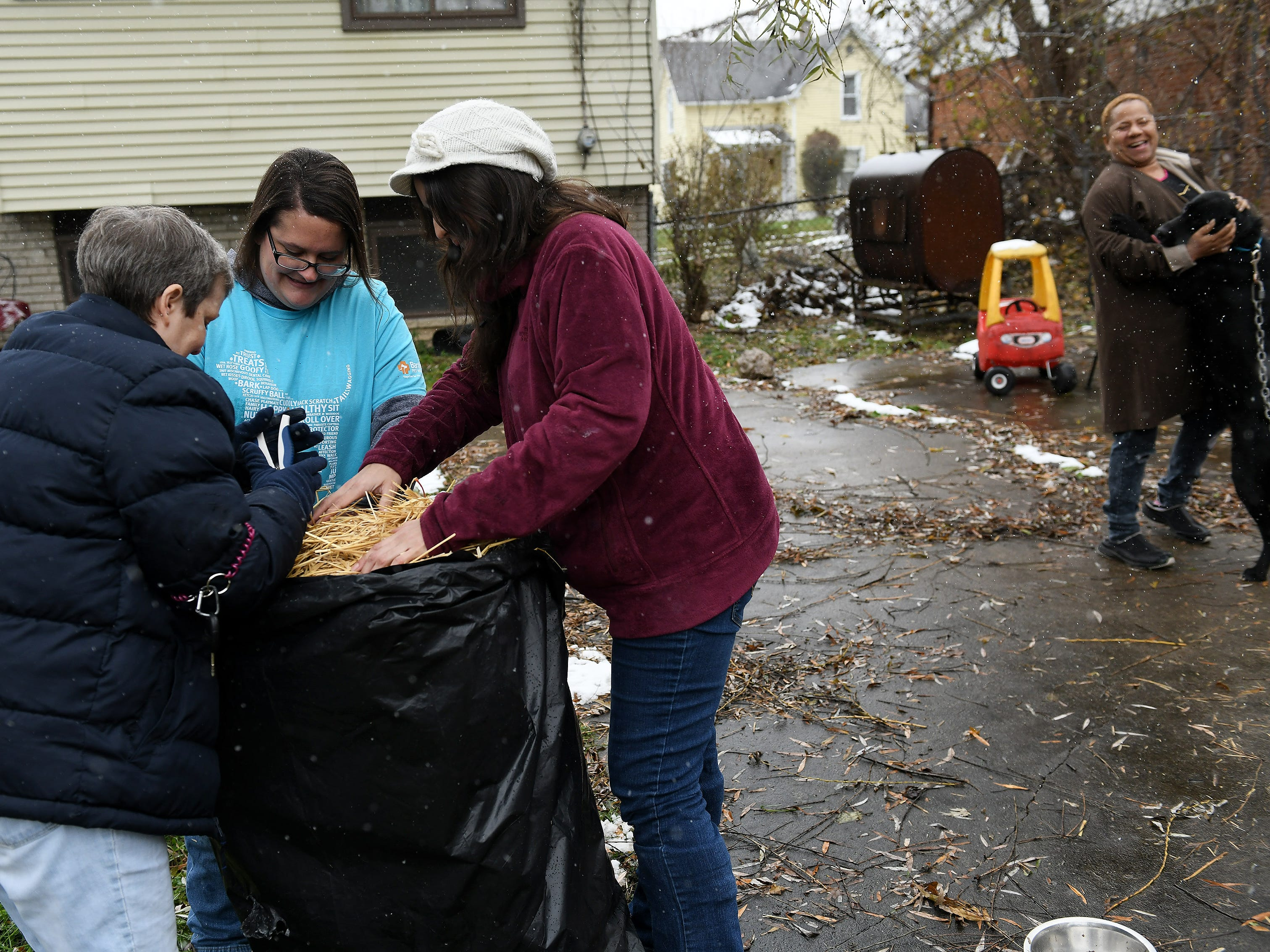 From left, Animal Care Network manager Lori Elliott, and Kelly Abate and Elizabeth Vega, two volunteers from Banfield Pet Hospital, cut loose a bale of straw for the doghouse of Black, right, with his owner's daughter, Renee Greenhouse, at their home in Pontiac.