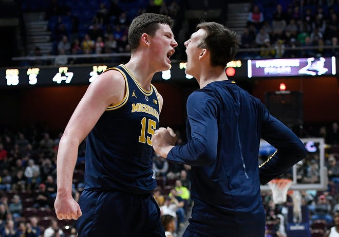 Michigan's Jon Teske (15) celebrates with teammate Colin Castleton during the first half.