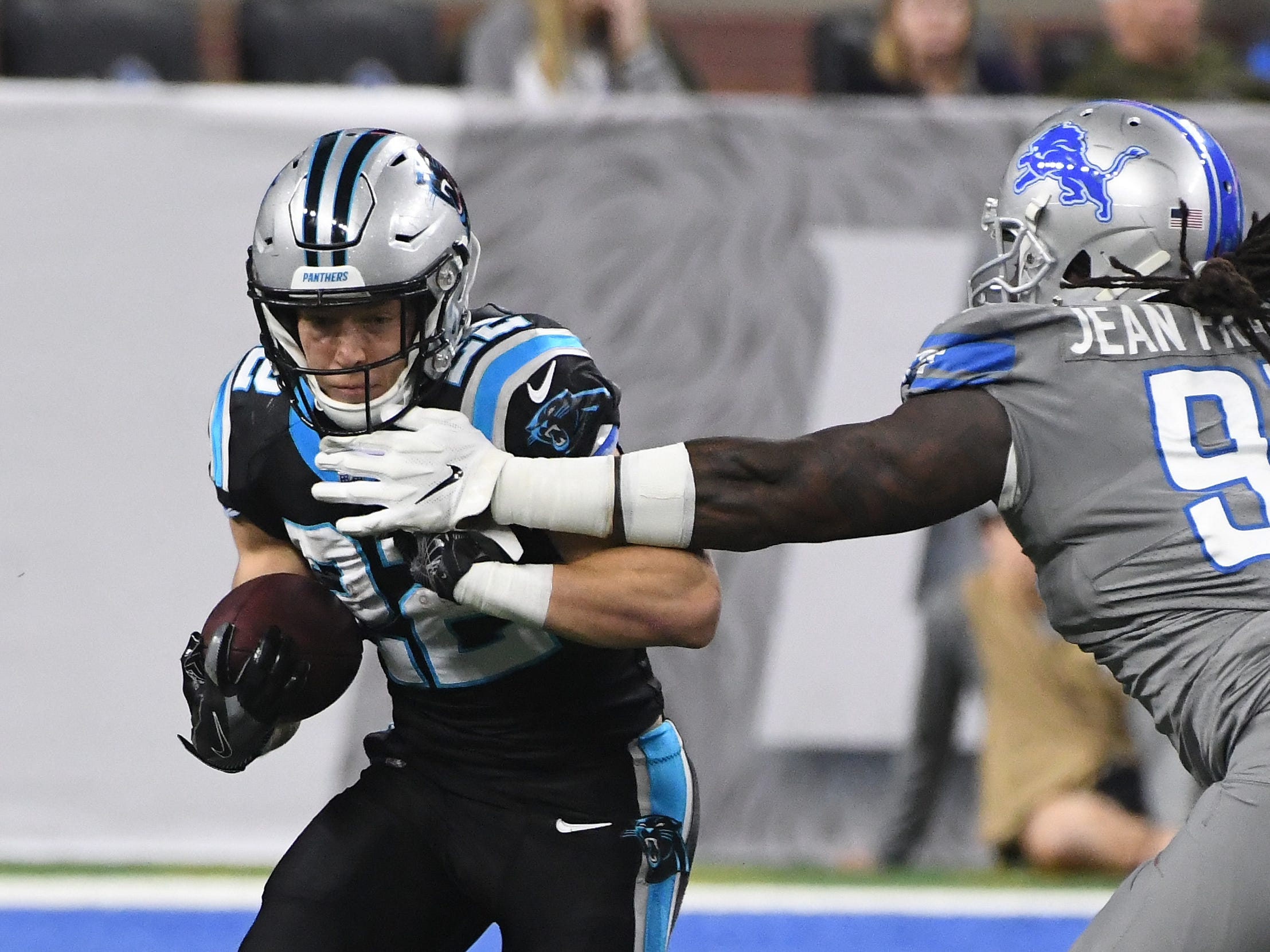 Panthers running back Christian McCaffrey gets around Lions' Ricky Jean Francois on a run in the second quarter.