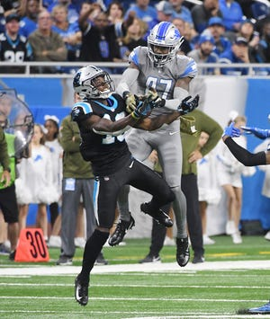 The Lions' Tracy Walker rips away a pass intended for the Panthers' Curtis Amuel for the interception late in the second quarter.