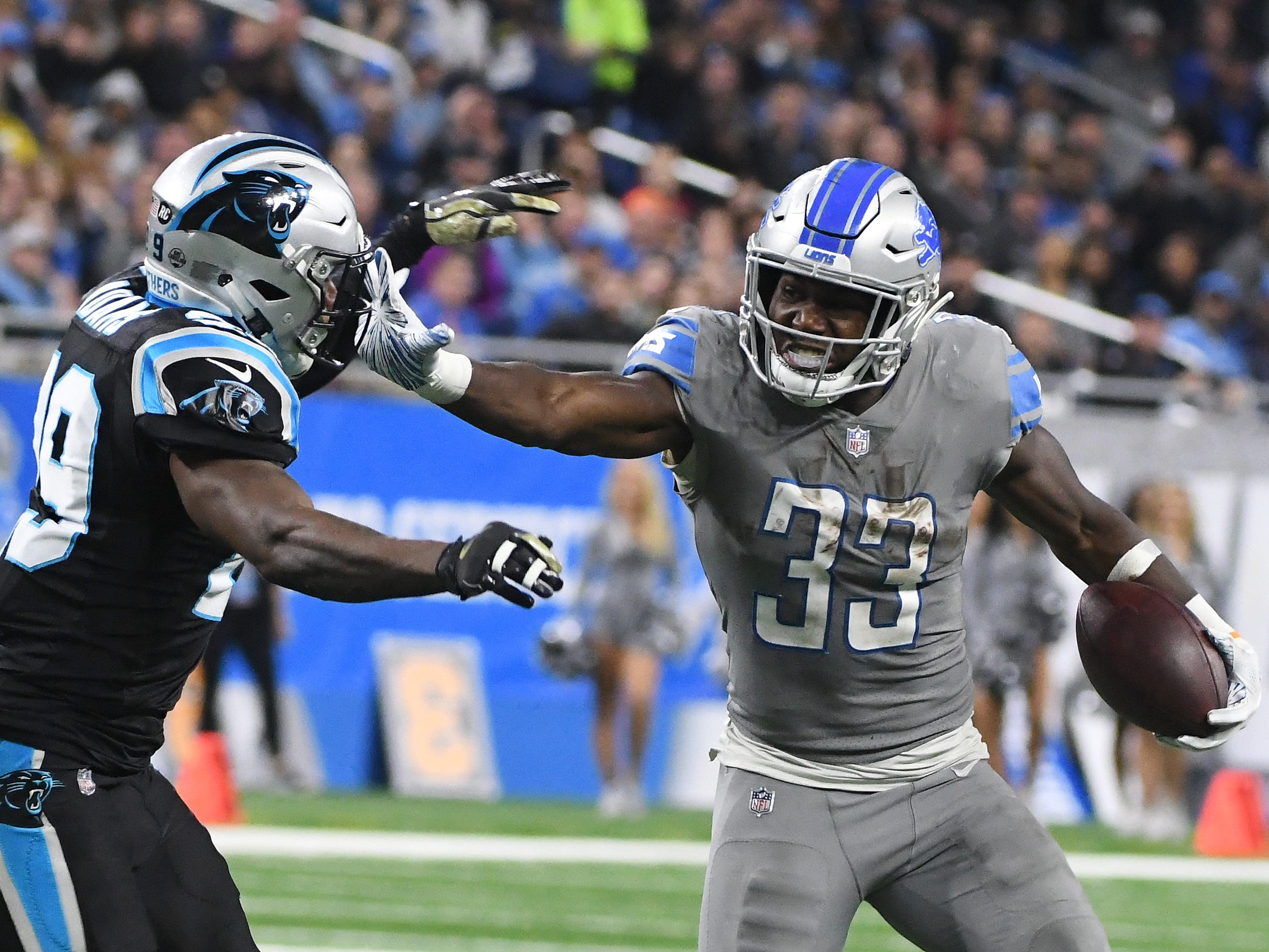Lions running back Kerryon Johnson stiff arms Panthers' Mike Adams on a run in the third quarter.