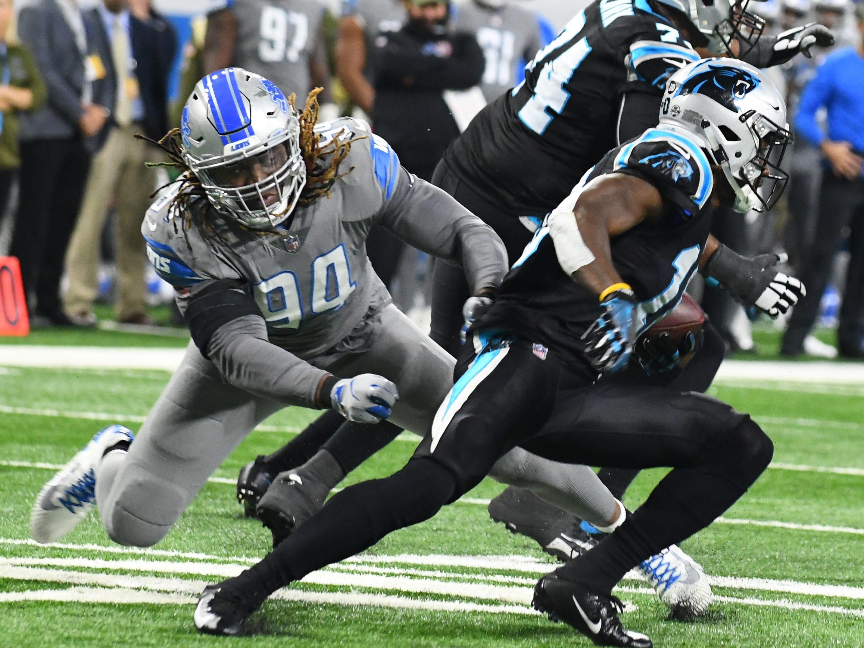 Lions' Ezekiel Ansah slows down Panthers' Torrey Smith, with the defense finishing the job for a loss in the fourth quarter.