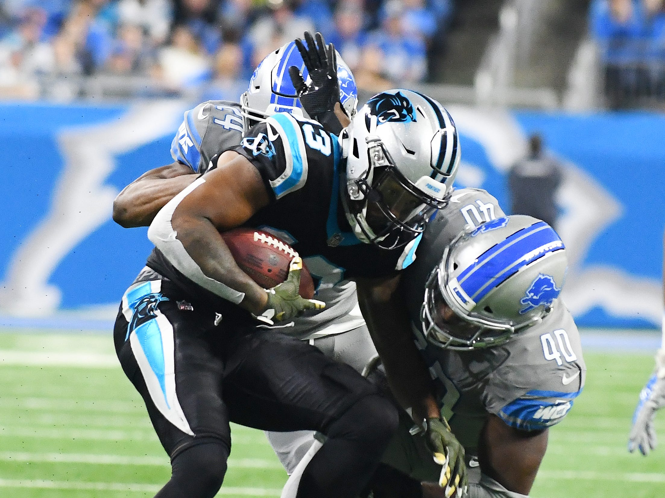 Lions' Nevion Lawson and Jarrad Davis bring down Panthers wide receiver Jarius Wright in the second quarter.