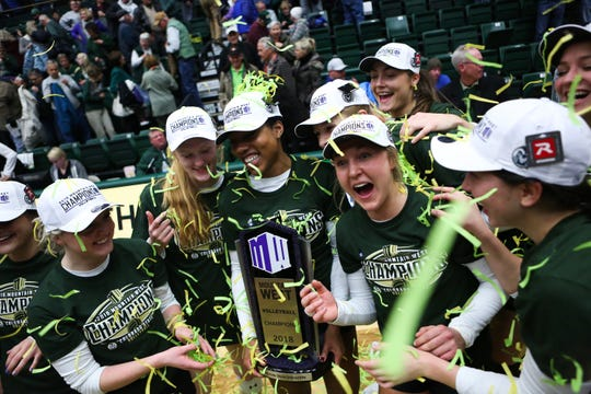 Members of the CSU volleyball team celebrate winning the Mountain West championship after Saturday's match at Moby Arena.