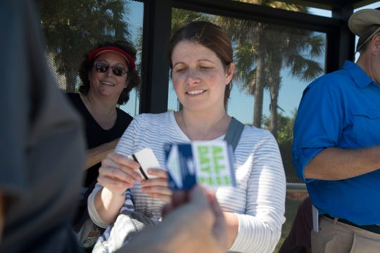 Krista Callahan, a City of Fort Myers employee, gets out her bus pass for the next leg of Saturday's Homeless Challenge, a walk-in-their-shoes experience organized by Lee County Homeless Coalition.