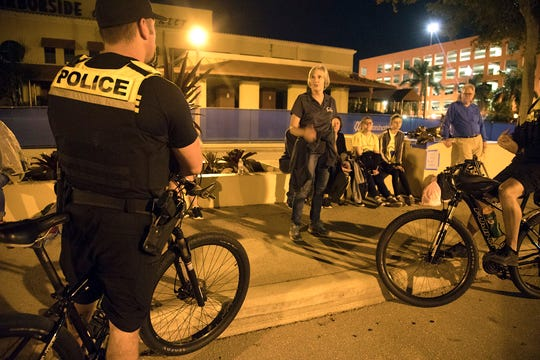 Known on the streets as 'the bumblebees' for their yellow and black garb, Officers Michael Prechard.(left) and Richard Carpenter of the Fort Myers Police Department bike unit talk to Homeless Challenge participants on Saturday evening about their interaction with the area homeless population.