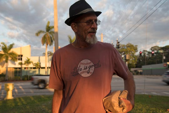Homeless Challenge participant Jeff Meyers carries a brown bag dinner courtesy of Salvation Army to Lions Park in Fort Myers on Saturday. Meyers lived for 10 years on Charlotte County streets, surviving on odd construction jobs and tent camping in the woods until he landed a full-time job. Today he's married and owns a home.