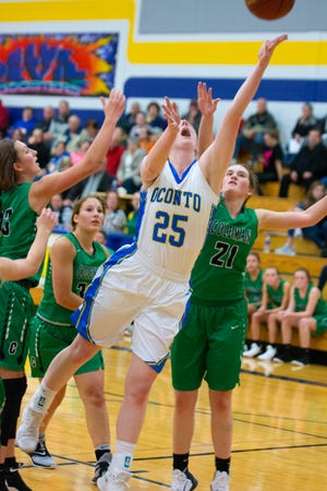 Oconto's Mara Allen stretches for one of her many rebounds in the basketball season opener against Coleman.