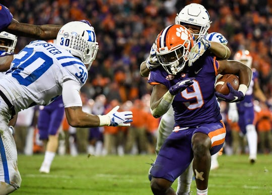 Clemson running back Travis Etienne (9) attempts to evade Duke safety Lummie Young IV (23) and safety Brandon Feamster (30) Memorial Stadium on Friday, Nov. 17, 2018.