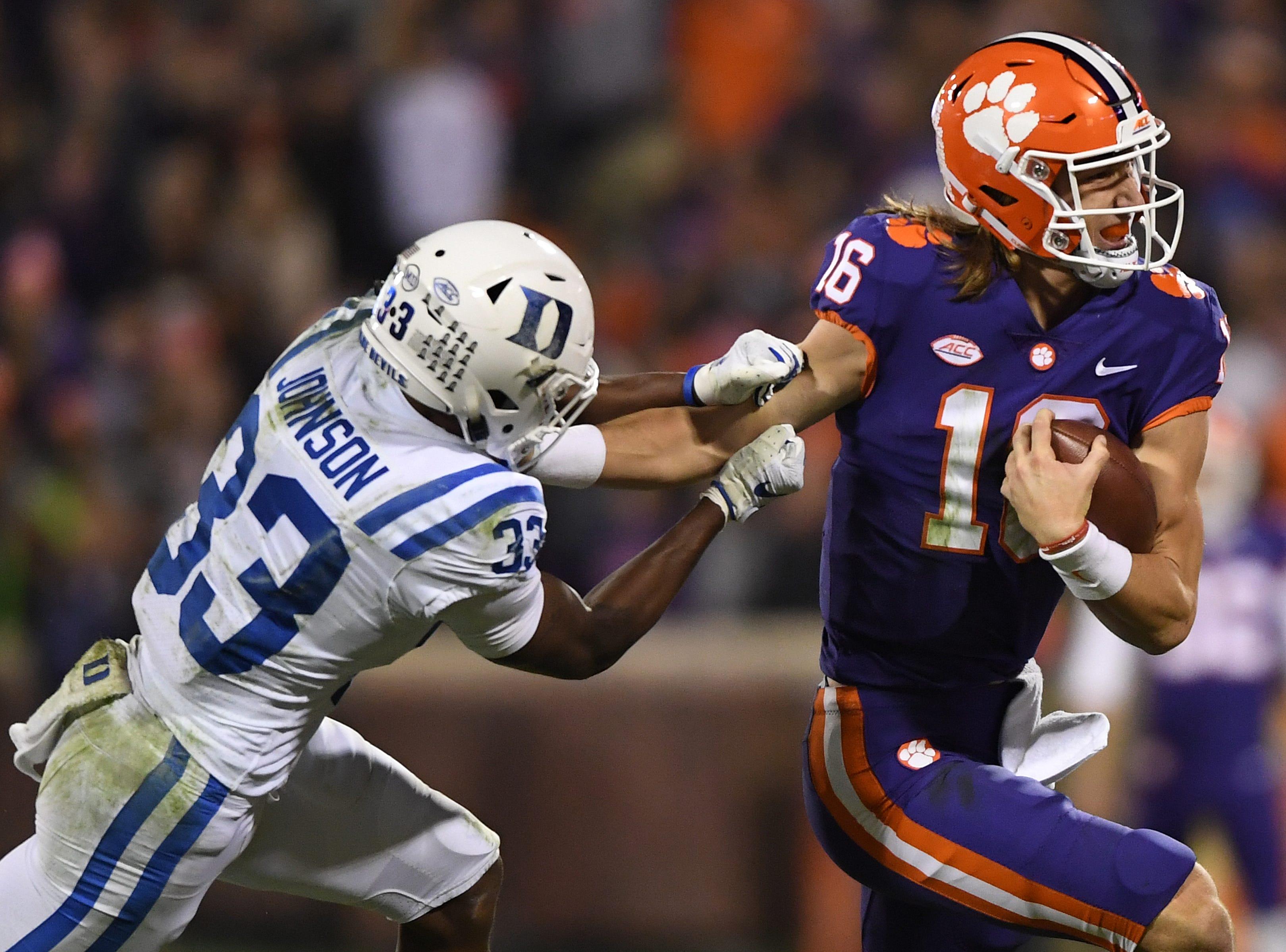Duke safety Leonard Johnson (33) tries to bring down Clemson quarterback Trevor Lawrence (16) during the 4th quarter Saturday, November 17, 2018 at Clemson's Memorial Stadium.