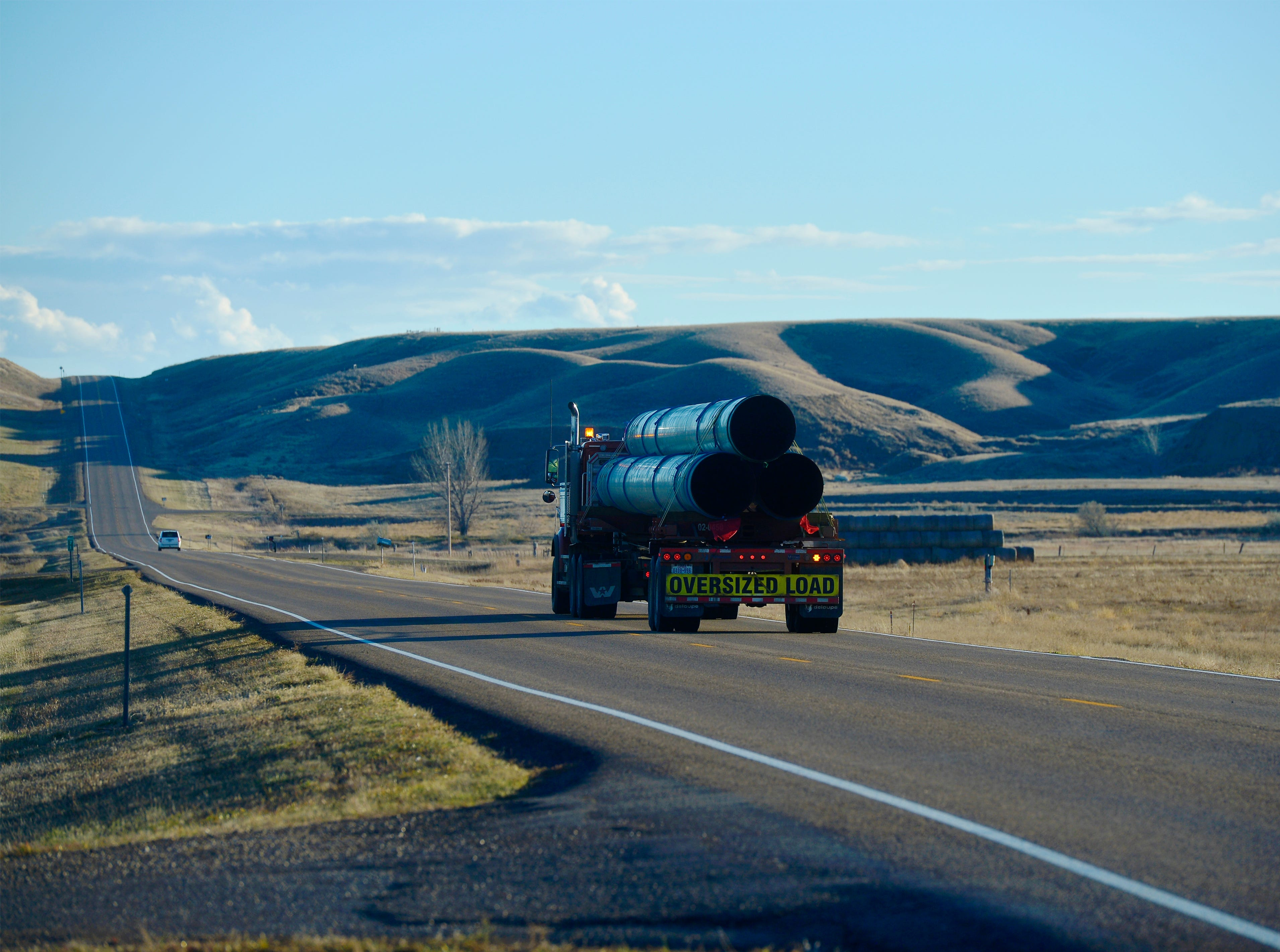 Pipe truck rumbles down the highway between Fort Peck and Glasgow.