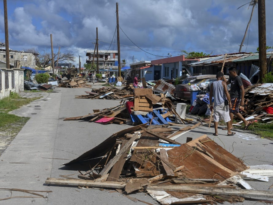 Civilians from the village of Chalan Konoa, Saipan, Commonwealth of the Northern Mariana Islands, move their debris piles to the middle of the road to aid the Guam Army National Guard in collecting the debris, Nov. 17, 2018, in support of the Super Typhoon Yutu relief efforts. Service members from Joint Region Marianas and U.S. Indo-Pacific Command are providing Department of Defense support to the CNMI's civil and local officials as part of the Federal Emergency Management Agency-supported Super Typhoon Yutu recovery efforts.