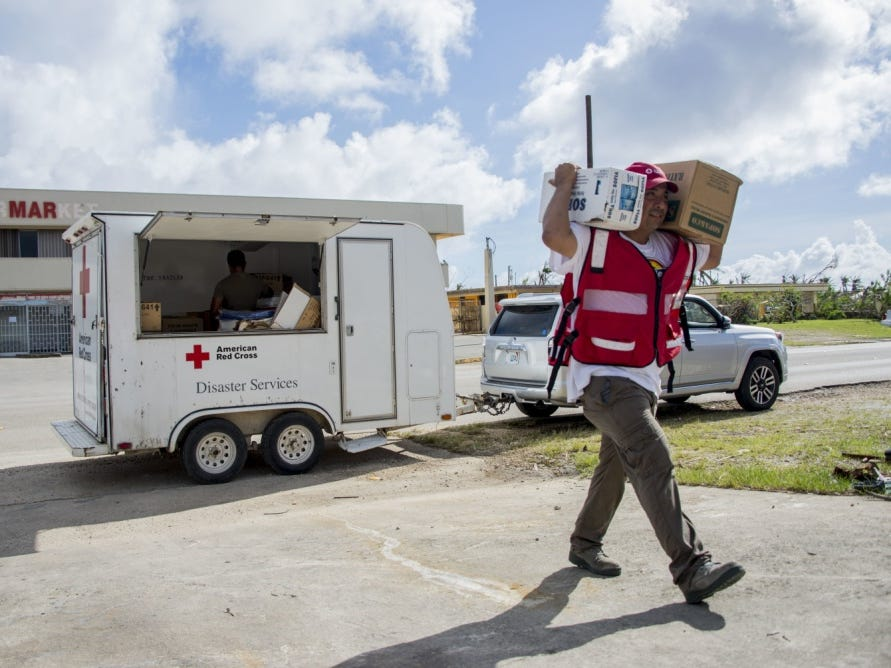 Saipan, Commonwealth of the Northern Mariana Islands, November 15, 2018 – Marc Acosta (right), an American Red Cross volunteer, distributes relief supplies to communities in need after Super Typhoon Yutu made landfall, damaging hundreds of homes and leaving many residents without shelter, power, food, or access to clean water.