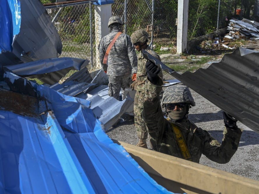 Sgt. Ken Orejola of the Guam Army National Guard's 721st Army Band, throws tin into the back of a large mobility vehicle during debris clearing operations in the village of Chalan Konoa, Saipan, Commonwealth of the Northern Mariana Islands, Nov. 17, 2018, in support of the Super Typhoon Yutu relief efforts.