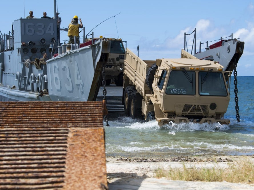 A U.S. Army light medium tactical vehicle assigned to the 9th Mission Support Command, Army Reserves, Honolulu, is driven off a U.S. Naval Landing Craft Utility operating out of the USS Ashland (LSD 48) during beach-front loading and unloading of vehicles on Saipan, Commonwealth of the Northern Mariana Islands, Nov. 12, 2018, as part of the Super Typhoon Yutu relief effort.