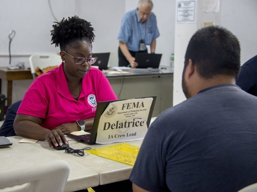 Tinian, Commonwealth of the Northern Mariana Islands, November 14, 2018 – A disaster survivor (right) registers for FEMA assistance after Super Typhoon Yutu damaged his home. FEMA Individual Assistance Crew Lead, Delatrice Perry (left) is one of many FEMA staff who have been deployed throughout the islands of Saipan, Tinian, Rota, and Guam to work in partnership with the Commonwealth to help people recover from the disaster.