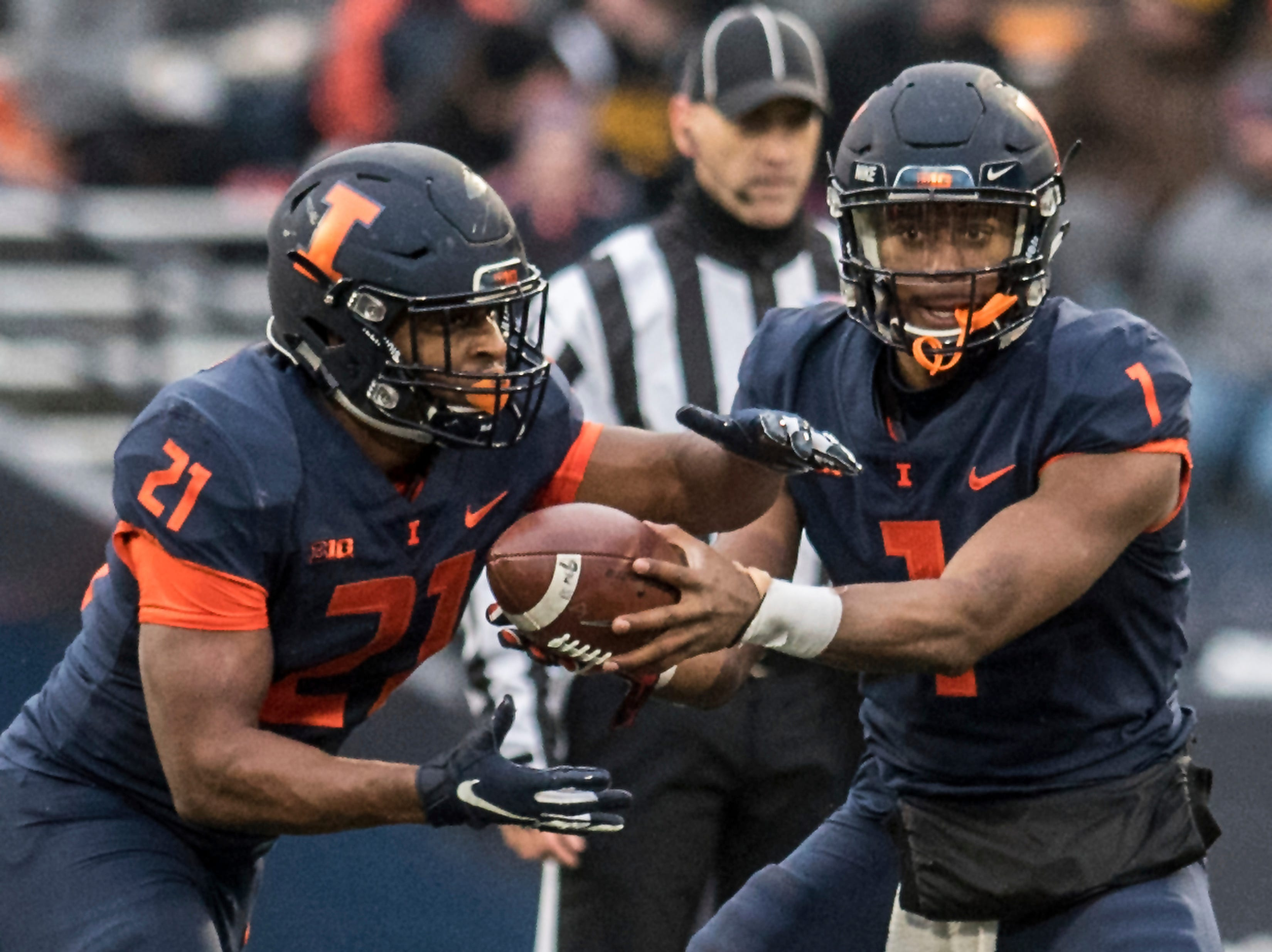 Illinois quarterback A.J. Bush, Jr. (1) hands off to running back Ra'Von Bonner (21) in the first half of a NCAA college football game against Iowa, Saturday, Nov. 17, 2018, in Champaign, Ill.