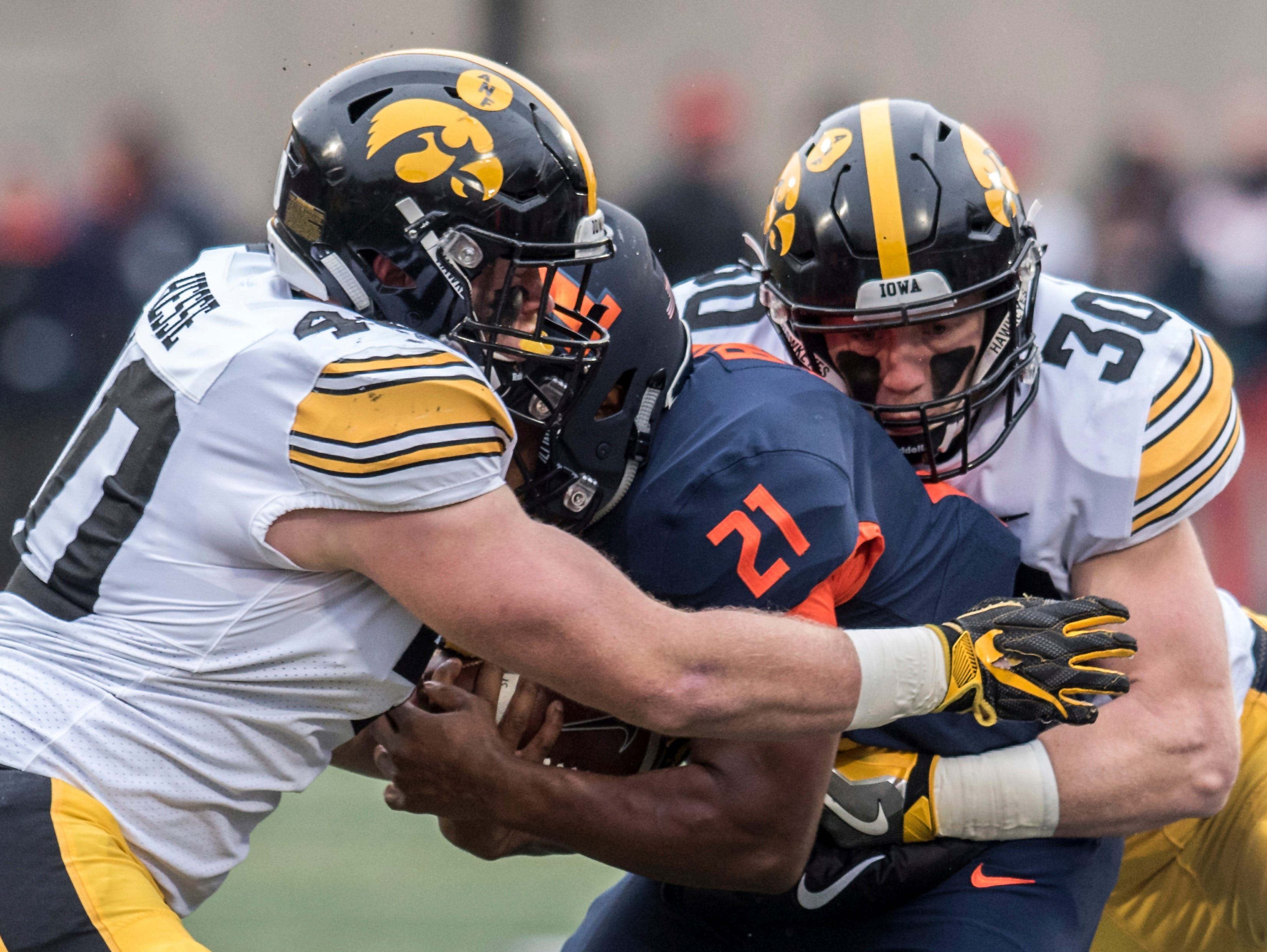 Iowa's Parker Hesse (40) and Jake Gervase (30) tackle Illinois' Ra'Von Bonner (21) in the first half of a NCAA college football game, Saturday, Nov. 17, 2018, in Champaign, Ill.