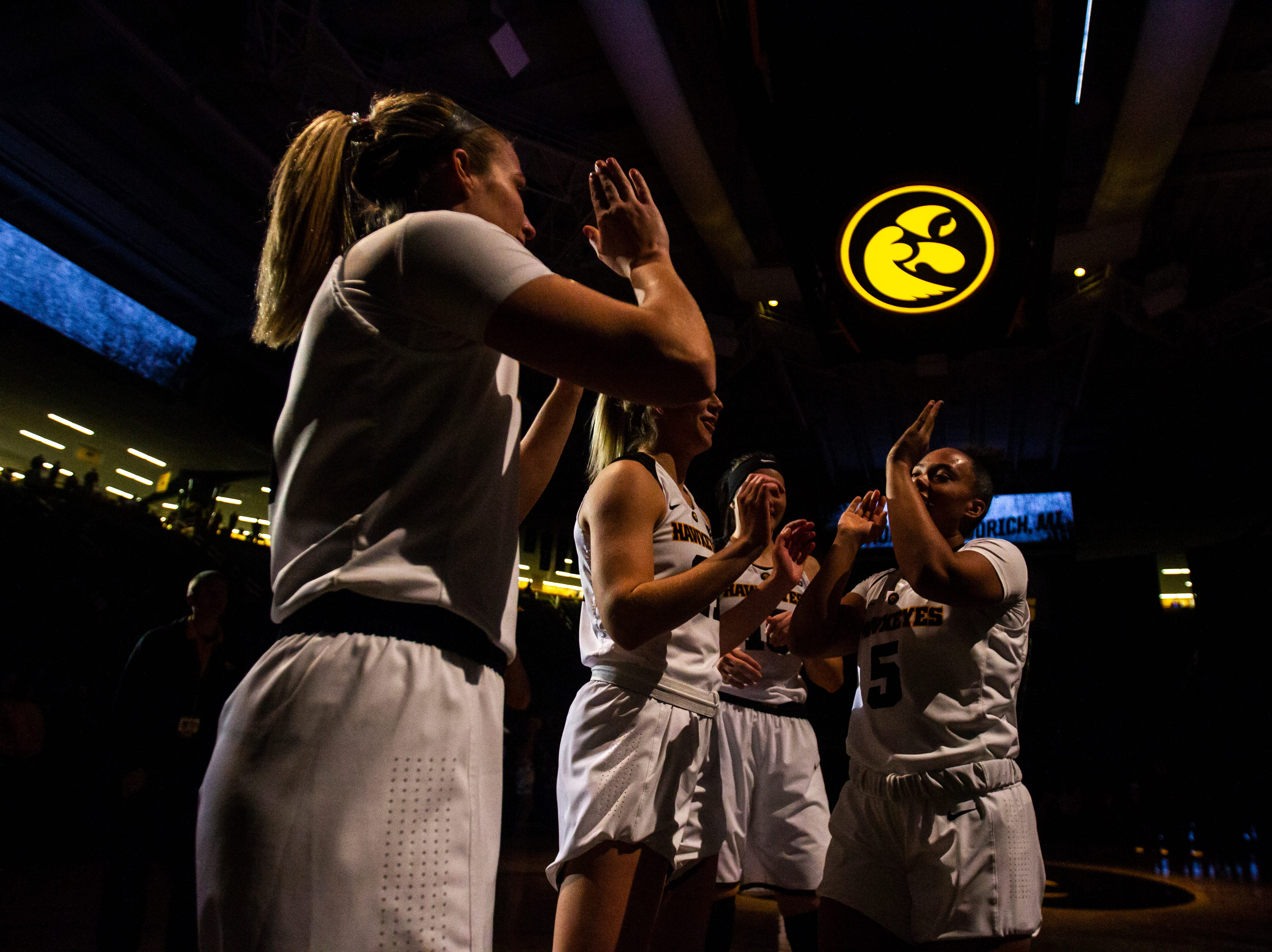 Iowa guard Alexis Sevillian (5) high-fives Hannah Stewart (21) during introductions before an NCAA women's basketball game on Saturday, Nov. 17, 2018, at Carver-Hawkeye Arena in Iowa City.