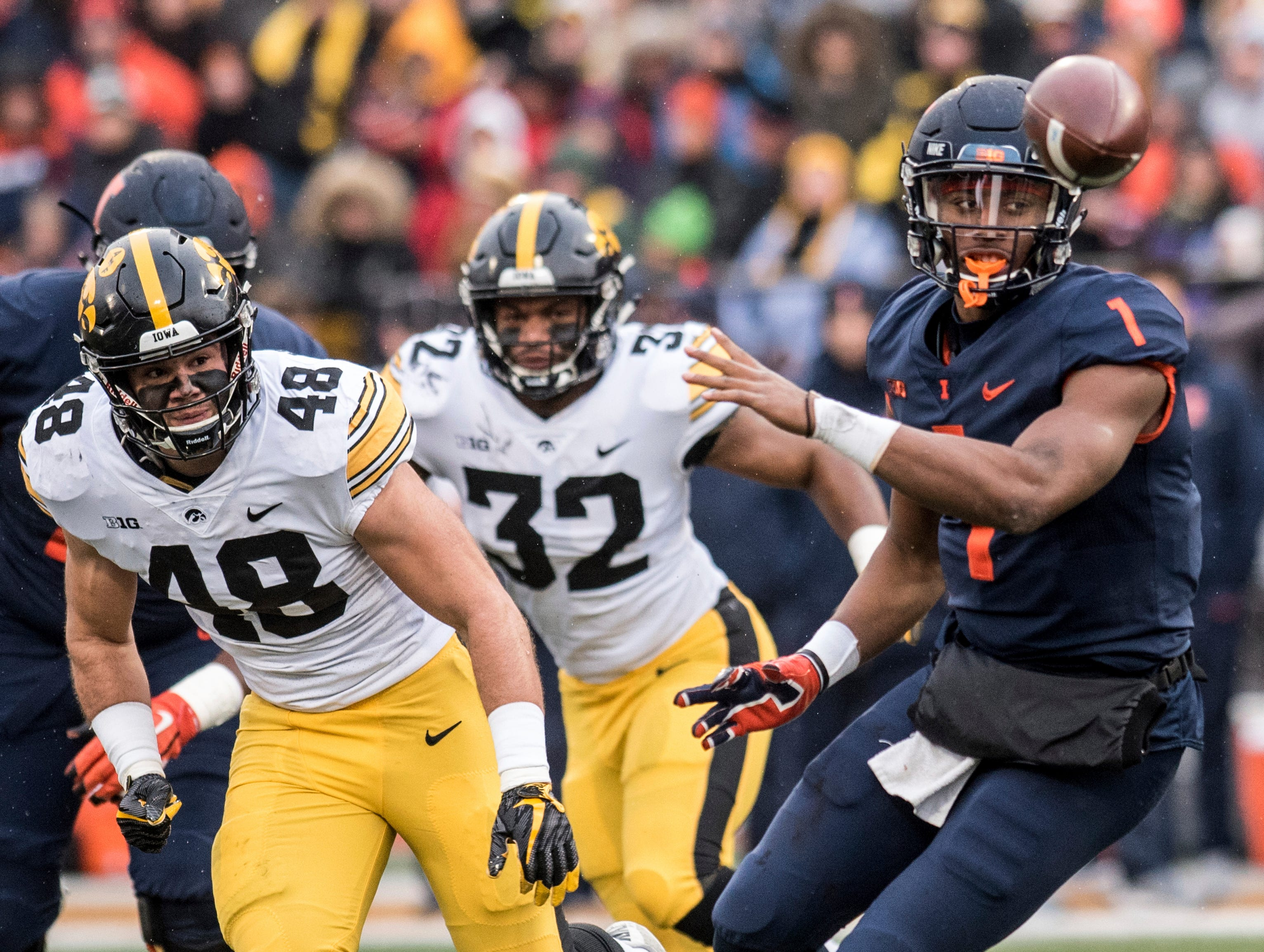 Illinois quarterback A.J. Bush, Jr. (1) throws a shuffle pass as Iowa's Jack Hockaday (48) and Djimon Colbert (32) defend in the first half of a NCAA college football game, Saturday, Nov. 17, 2018, in Champaign, Ill.