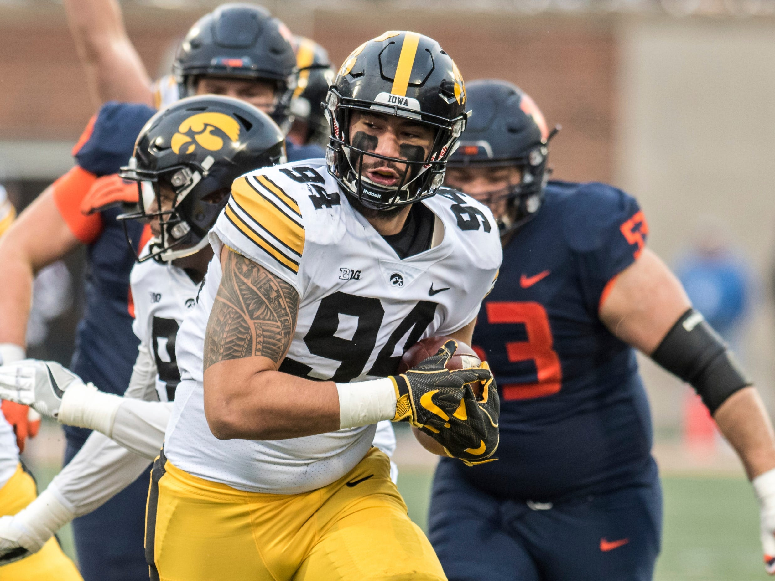 Iowa's A.J. Epenesa (94) runs the ball into the end zone after recovering a fumble in the first half of a NCAA college football game against Illinois, Saturday, Nov. 17, 2018, in Champaign, Ill.