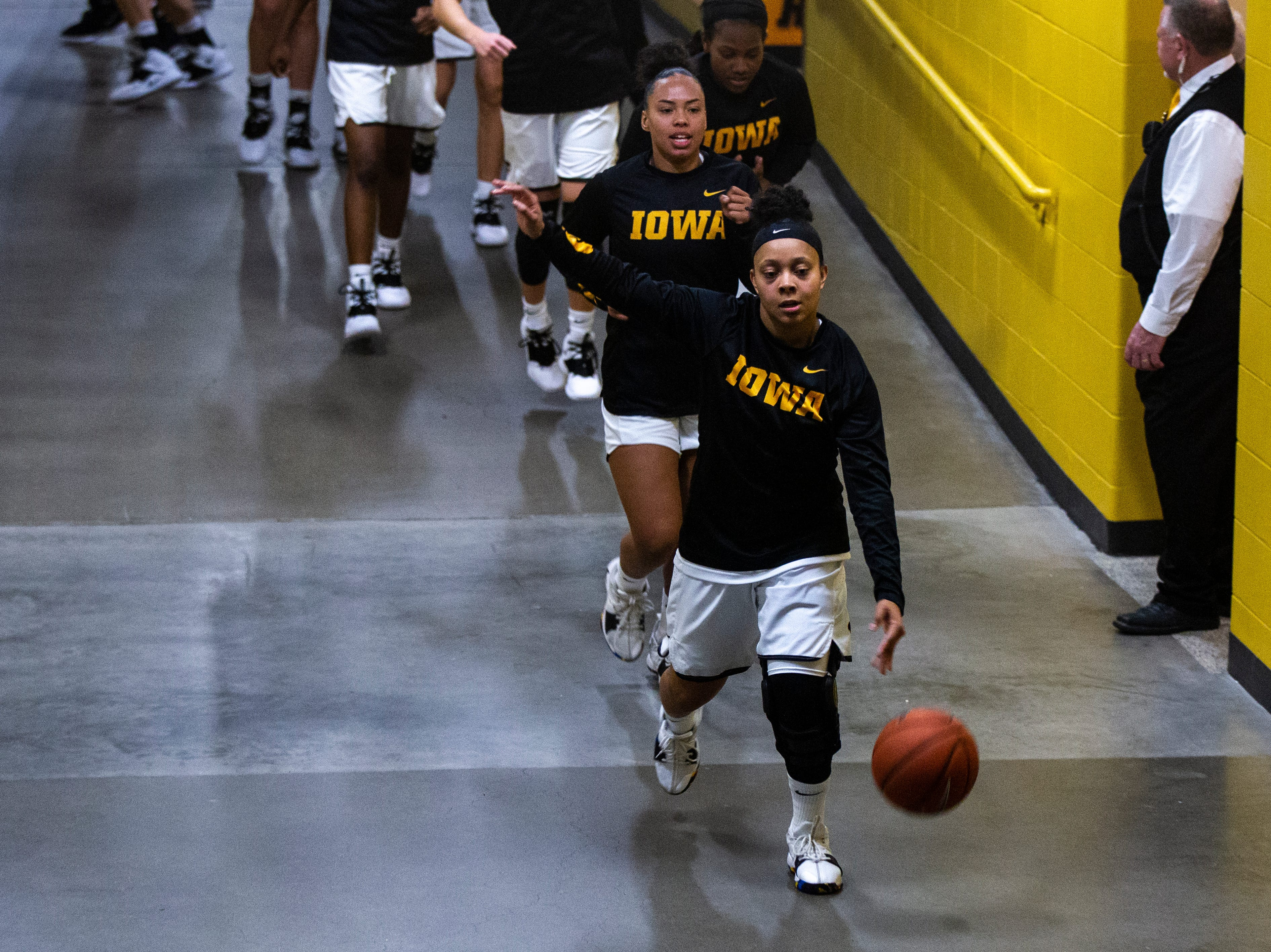 Iowa guard Tania Davis (front) dribbles a ball while making her way through a tunnel towards the court before an NCAA women's basketball game on Saturday, Nov. 17, 2018, at Carver-Hawkeye Arena in Iowa City.
