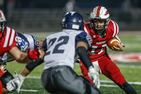 New Palestine High School's Zach Neligh (11) is tackled by  Michigan City High School' Nate Ware (22), during the I.H.S.A.A class 5A Semi-state game between New Palestine High School and Michigan City High School at New Pal. on Saturday, Nov. 17, 2018.