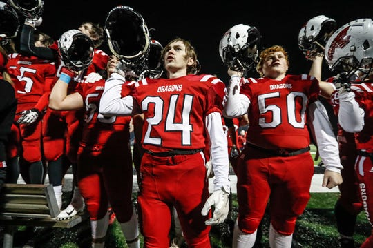 New Palestine High School football players and cheerleaders celebrate winning the I.H.S.A.A class 5A Semi-state game between New Palestine High School and Michigan City High School by singing their school fight song at New Pal. on Saturday, Nov. 17, 2018.