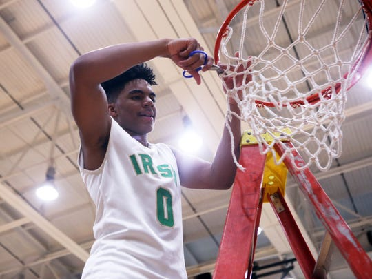 James Franklin helps cut down the net after Cathedral won the City tournament championship.