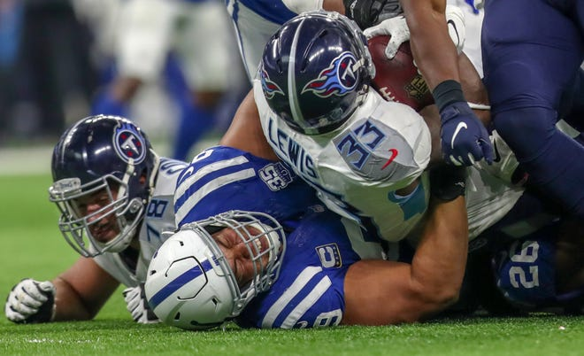 Indianapolis Colts defensive tackle Al Woods (99) pulls Tennessee Titans running back Dion Lewis (33) back on a third and short at Lucas Oil Stadium in Indianapolis, on Sunday, Nov. 18, 2018. The Titans would punt.