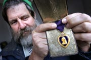 Richard Vonnegut (second cousin to Kurt), carefully displays Kurt Vonnegut's Purple Heart, from World War II in 2010.