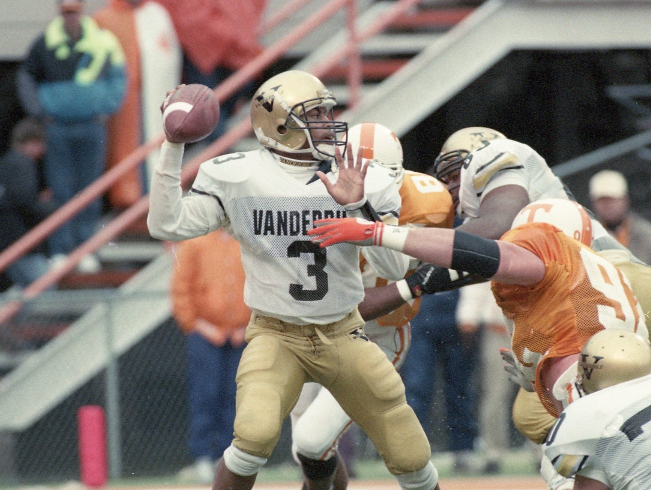Vanderbilt quarterback Ronnie Gordon (3) was pressed by Tennessee's defense all day. Tennessee's Shane Boham reaches for Gordon during first half play on November 27, 1993.