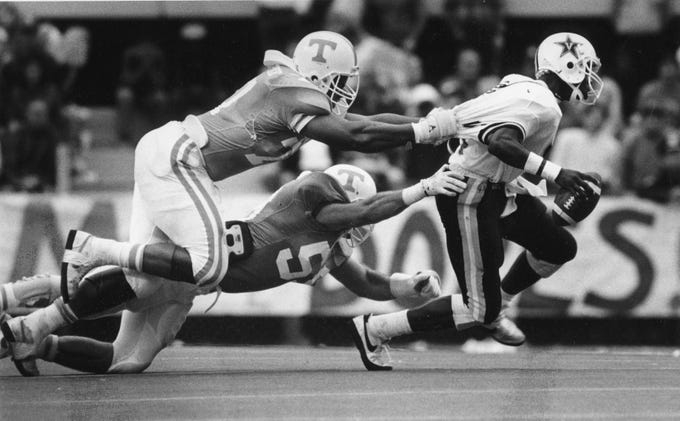 Tennessee's Richard Cooper (77) and Marr Houanic (59) tackle Vanderbilt's Eric Jones in the fourth quarter on November 28, 1988. J. Miles Cary