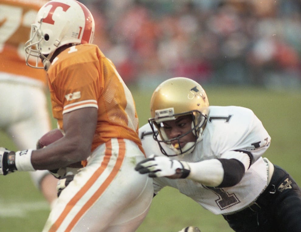 Tennessee's Joey Kent (11) gains yardage before Vanderbilt's Fred Vinson (1) comes information the tackle on November 25, 1995.