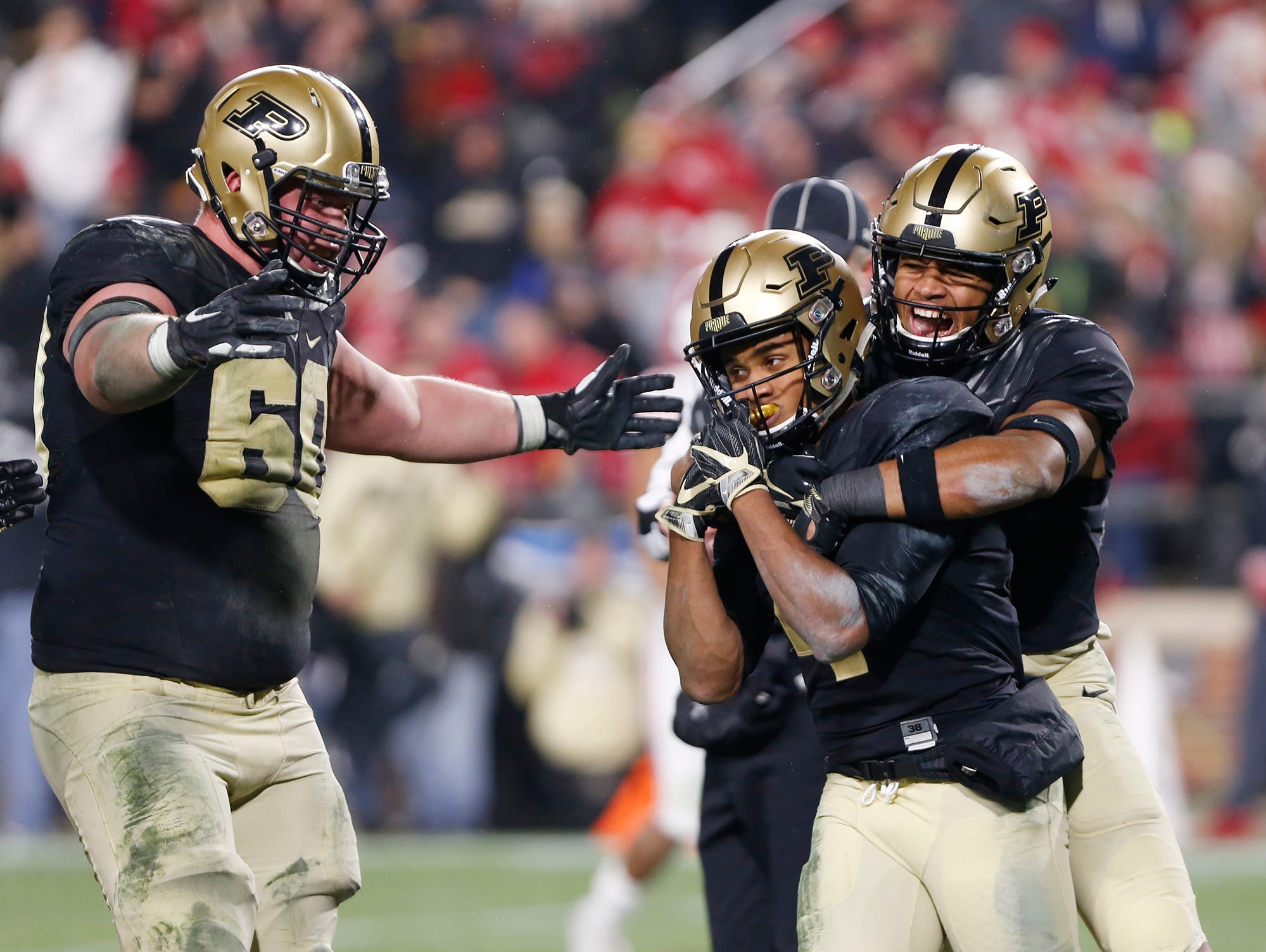 Rondale Moore of Purdue celebrates with teammates Jared Sparks and Eric Swingler, left, after his touchdown reception with 57 seconds remaining in the third quarter against Wisconsin Saturday, November 17, 2018, at Ross-Ade Stadium. Purdue fell to Wisconsin 47-44 3OT.
