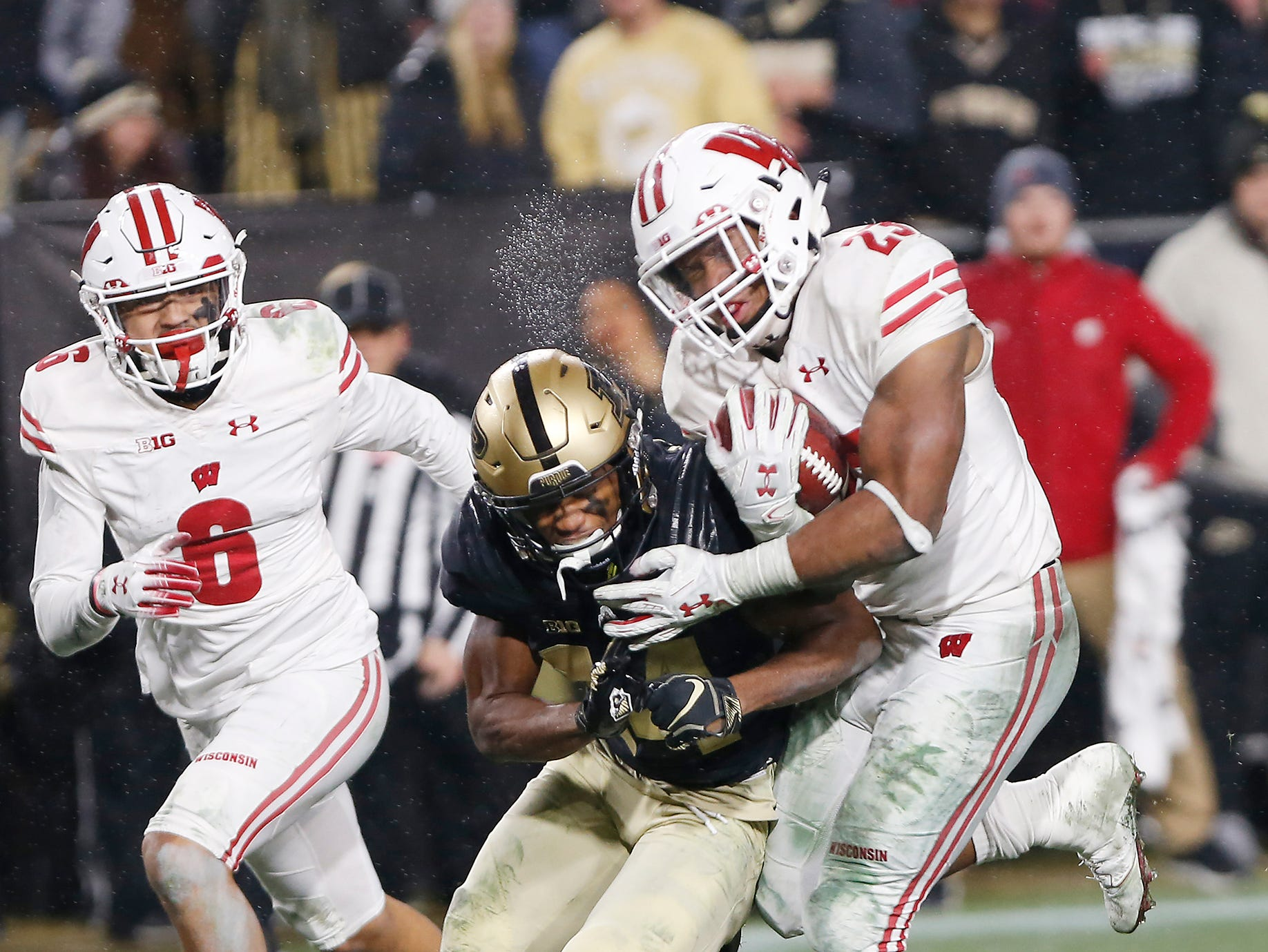 Jonathon Taylor of Wisconsin runs over Antonio Blackmon of Purdue as he rushes for the winning touchdown in the third overtime period Saturday, November 17, 2018, at Ross-Ade Stadium. Purdue fell to Wisconsin 47-44 3OT.